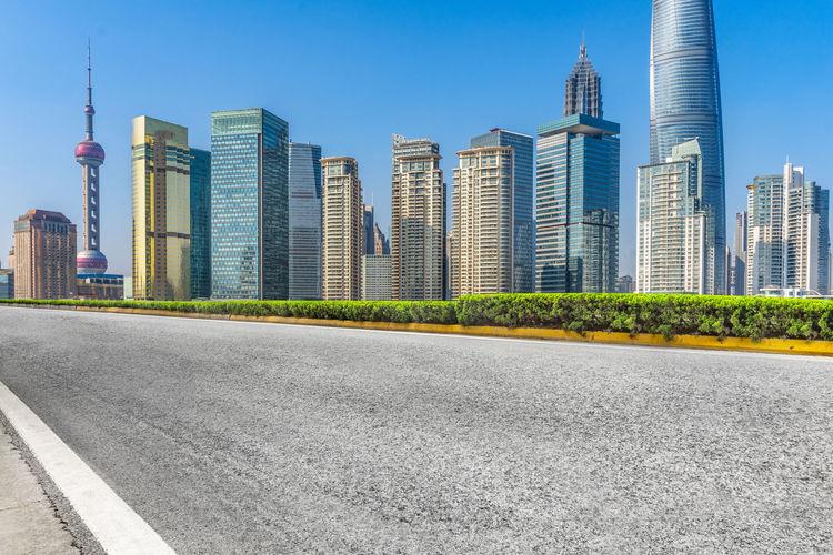 City street by modern buildings against clear sky