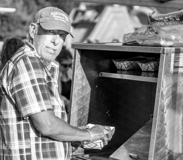 A hot dog vendor at work in Seattle. #urbanana: The Urban Playground Hot Dogs Adult Cap Casual Clothing Emotion Happiness Hot Dog Seller Hot Dog Stand Hot Dog Vendor Lifestyles Males  Men Mid Adult Men Occupation One Person Real People Smiling Standing Waist Up Working