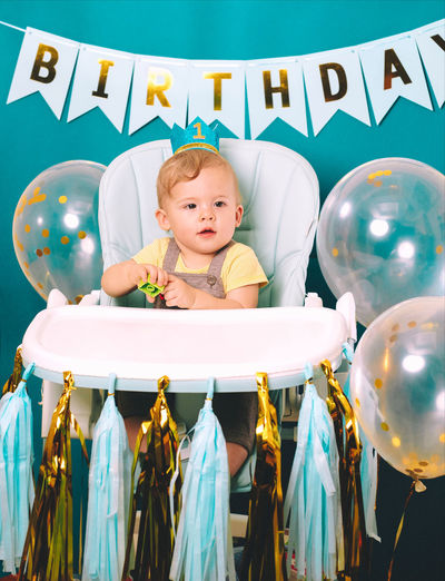 Cute baby boy sitting on high chair in birthday party