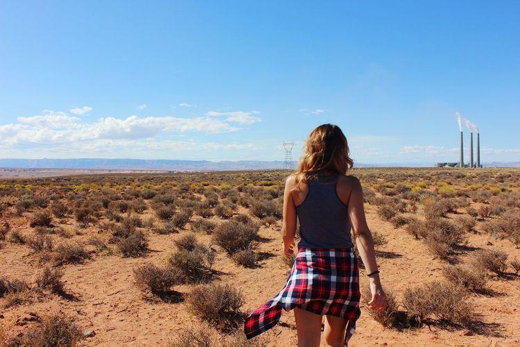 Rear View Of Woman Walking On Landscape Against Sky