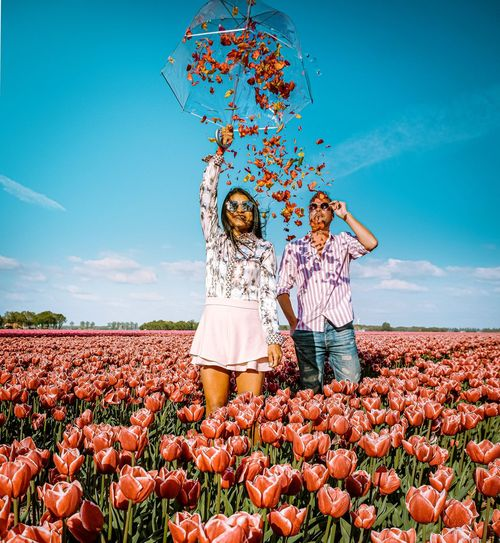 Couple standing amidst tulip farm with umbrella
