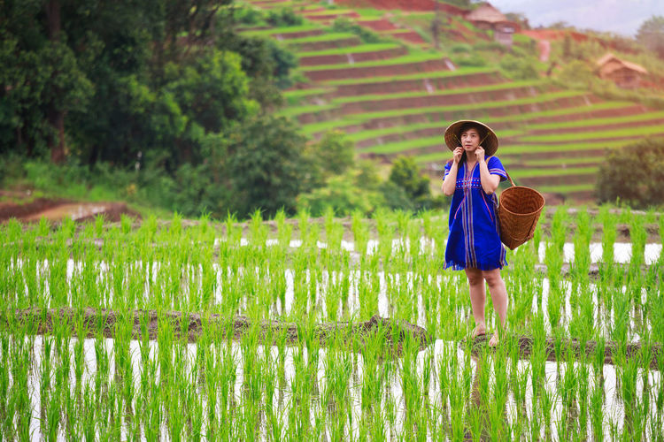 Woman wearing hat with container standing amidst field
