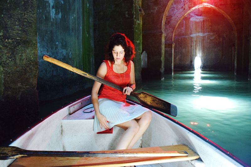 Woman sitting in boat on canal at illuminated tunnel