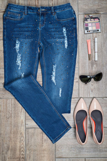 Flat lay of jeans with make-up and personal accessories on wooden floor