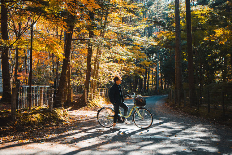 Man riding bicycle on street during autumn