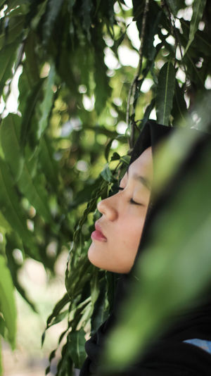 Close-up of woman with eyes closed by plants