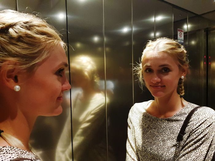 Young woman reflecting on mirror in elevator