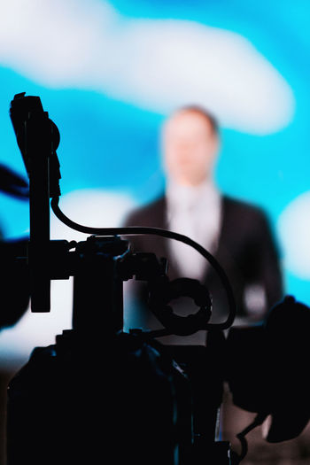 Camera Recording Presentation of a Speaker Media Press Conference Silhouette Camera Speaker News Reportage Presentation Communication Public Event Technology Equipment Speech Meeting Seminar Television Politician Politics Entertainment Bussiness Jurnalist Government Stage Corporate Live Leadership Campaign Correspondent Broadcast Blue Indoors  Unrecognizable Person
