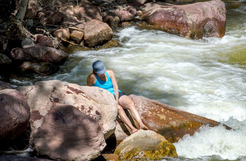 a Barefoot young woman enjoys the sounds of the rushing waters in the eldorado canyon state park Eldorado Canyon State Park Tourism Park Travel Environment Day Scenic Rock Pine Tree Summer Colorado Outdoor America Beautiful Rocky View Country Vacation Nature Hiking Majestic Wild Wilderness Natural Conservation Area Beauty Landscape Recreation  Geology Ethereal USA Scenery Eldorado Springs State Park  Boulders Layered Rocks Woman Relaxing Horizontal White Water Rapids River Water Female Casual Clothing Holiday Caucasian
