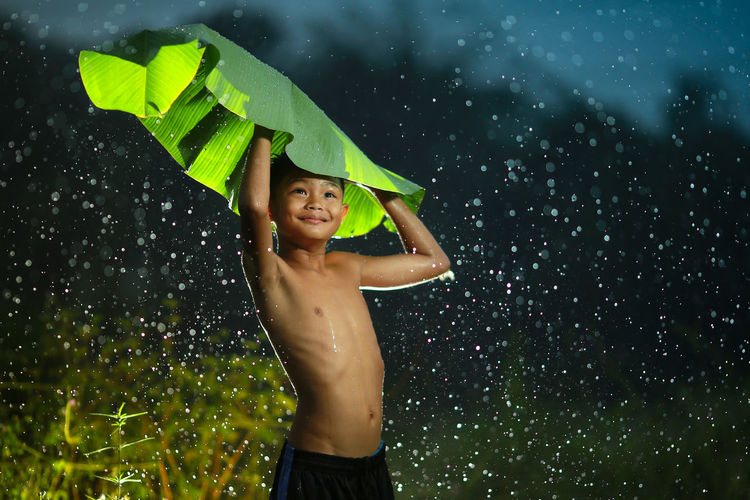 SINGLE BOY MADE BANANA LEAF AS COVER FROM RAINNING Cheerful Child Emotion Enjoyment Front View Happiness Human Arm Innocence Leisure Activity Looking Nature One Person Rain Shirtless Smiling Standing Three Quarter Length Waist Up Water Wet