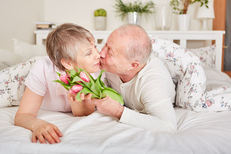 Midsection of couple kissing on bed
