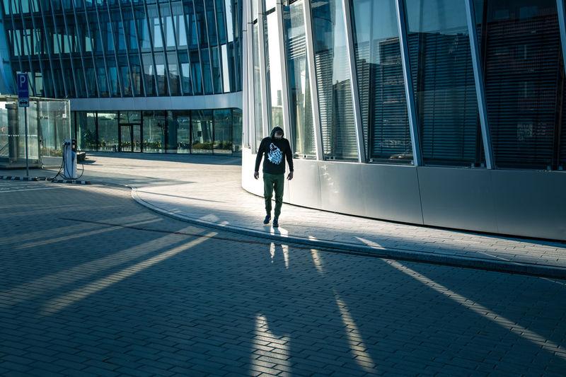 Rear view of woman walking on footpath against buildings