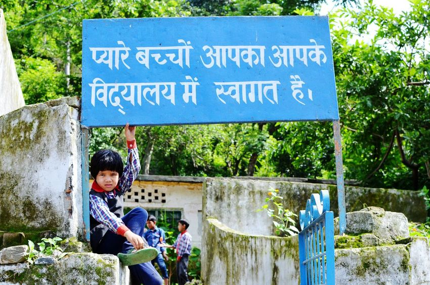 "The sign says, ""My dear kids, this is yoir own school and it welcomes you"" The kids are encouraged to in every means to start their preliminary education in these small scale schools, an effort to educate the next generation of this rural world. A little shy, a little friendly this lovely girl was sitting on one of the pillars of the school main entrance gate, allowed me to photograph her. Travel Diaries Education Little Girl Signboard Message Rural Rural Lifestyle Rural Life Rural Living From My Point Of View Encouragement 35mm Nikon Travel Photography in Uttarakhand India"