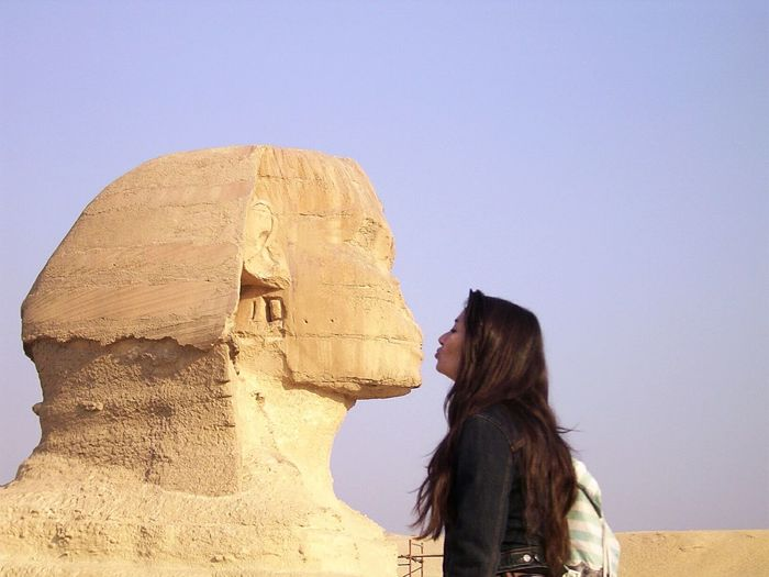 Optical illusion of woman kissing sphinx at great pyramid of giza