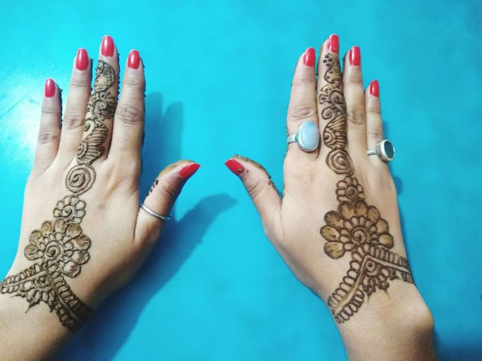 Cropped hands of woman showing henna tattoo at blue table