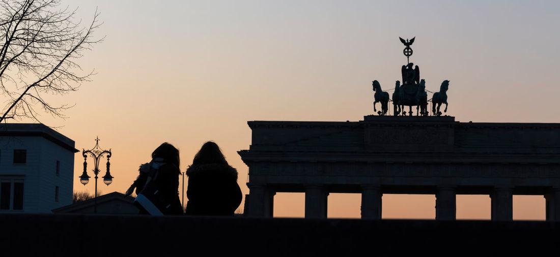 brandenburger tor berlin germany with people in th sundown Berlin Brandenburg Gate People Watching Architecture Brandenburger Tor Built Structure Evening Sky Sculpture Statue Sundown Sunset Travel Destinations