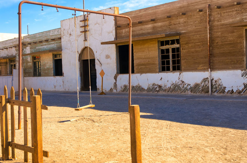 Swingset outside an abandoned school in Humberstone, Chile America Architecture Atacama Building Chile Derelict Desert Heritage Historic Houses Humberstone Industrial Industry Iquique Landscape Museum Nitrate Old Ruins Saltpeter Saltpetre South Town UNESCO World Heritage Site Work