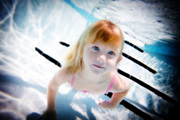 Portrait of cute girl swimming in pool