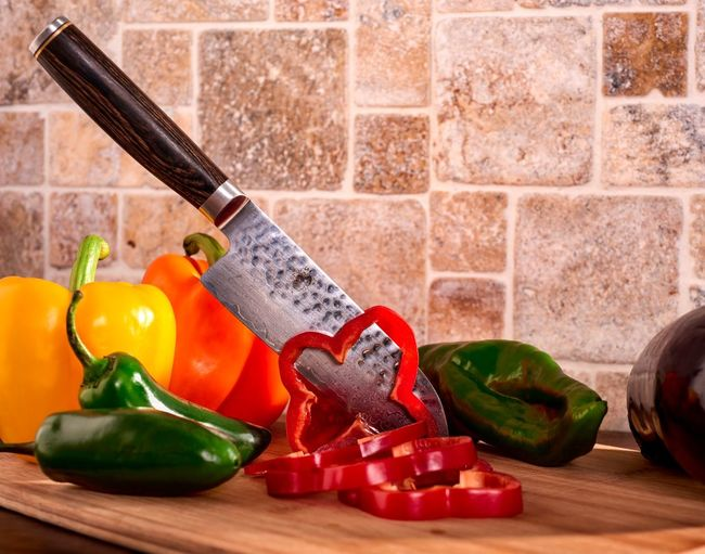 Close-up of bell peppers and knife on table