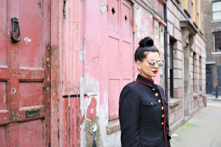 Woman wearing sunglasses while standing against wall in city
