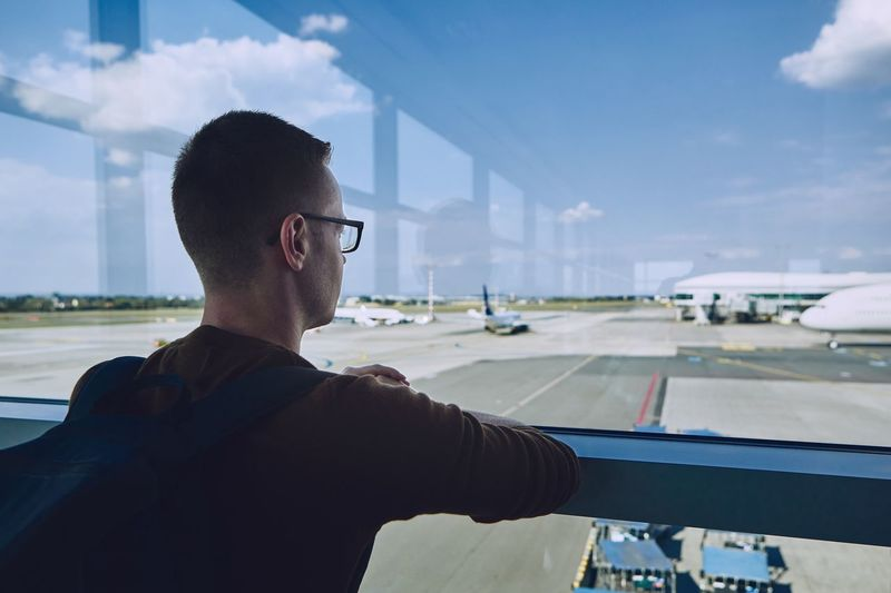 Man Looking At Airport Runway Through Window