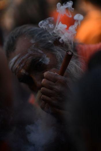 Old man smoking. smoking chillum. sadhu smoking in india. kumbh mela.