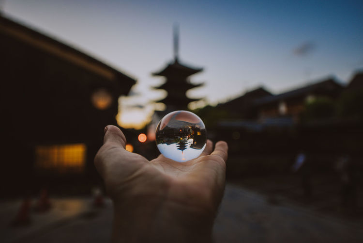 Midsection of person holding crystal ball against building