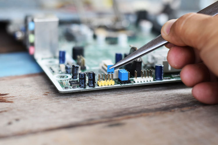 Cropped hand of technician repairing mother board at work shop