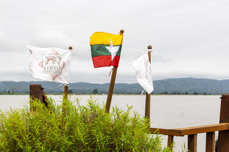 The burmese flag in the wind against mountains