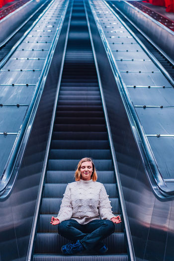 Woman meditating while sitting on escalator