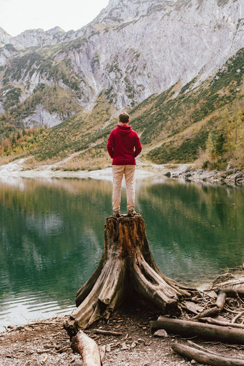 Rear view of man standing on tree stump by lake against mountains