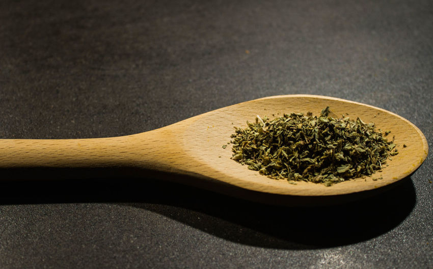 Close-up of dry leaves in wooden spoon on table