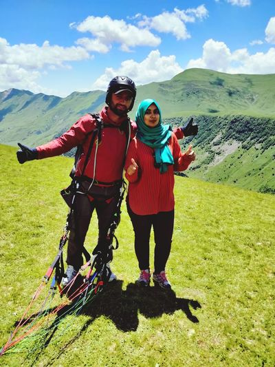 Portrait Of Couple Gesturing Peace Sign While Standing On Mountain