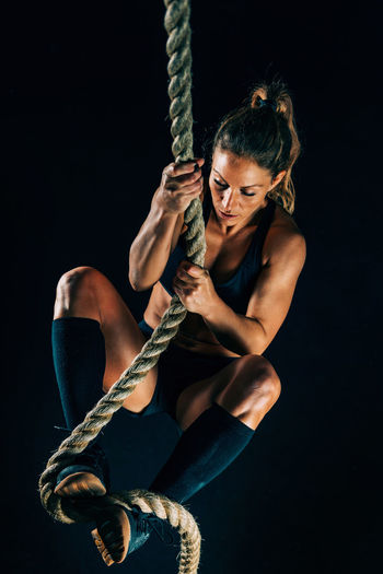 Cross Training. Rope Climbing Exercise Cross Training Fit Fitness Workout Climbing Rope Female Exercising Exercise Lifestyle Healthy Young People Sportswear Sport Woman Athlete Activity Body & Fitness Pulling Equipment Muscular Build Gym Caucasian Active Strength Black Background Indoors  Strong Sportswoman Endurance Power Physical Sporty Determination Attractive Beautiful One Woman