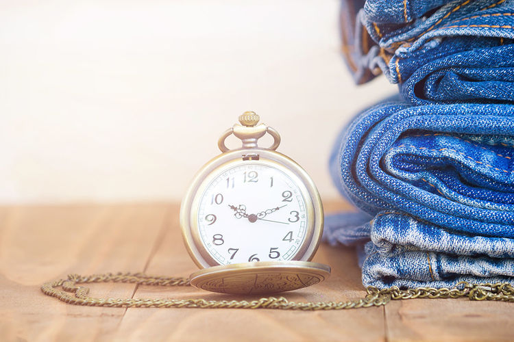 Close-up of pocket watch by stacked jeans on table