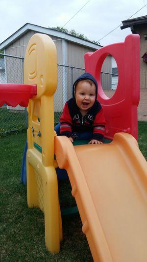 Cute cheerful kid sitting on plastic slide at back yard