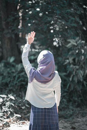 Rear view of woman with arms raised standing outdoors