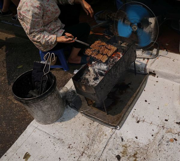 Low section of person cooking food on barbecue grill
