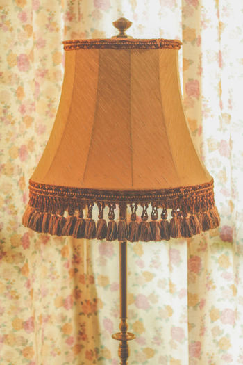 Close-up of lamp hanging on floor at home