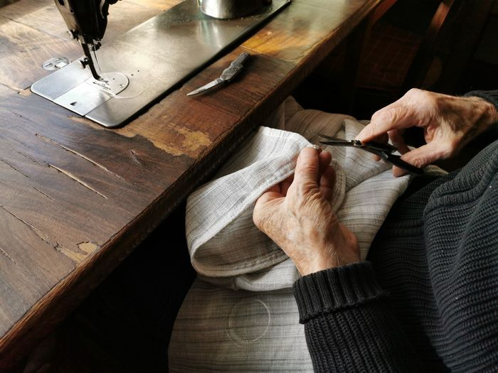 High angle view of man hands. old man, tailor, sewing, fabric.