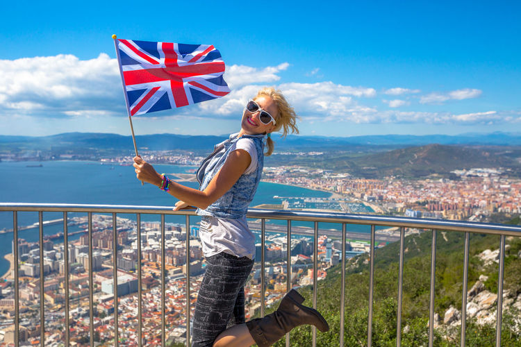 Portrait of smiling woman holding british flag while standing against cityscape