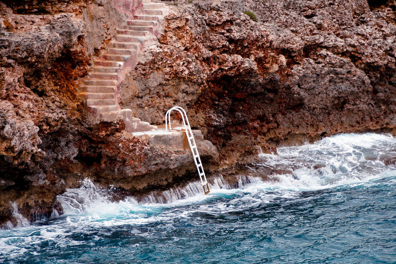 Water flowing through rocks by sea and stairs