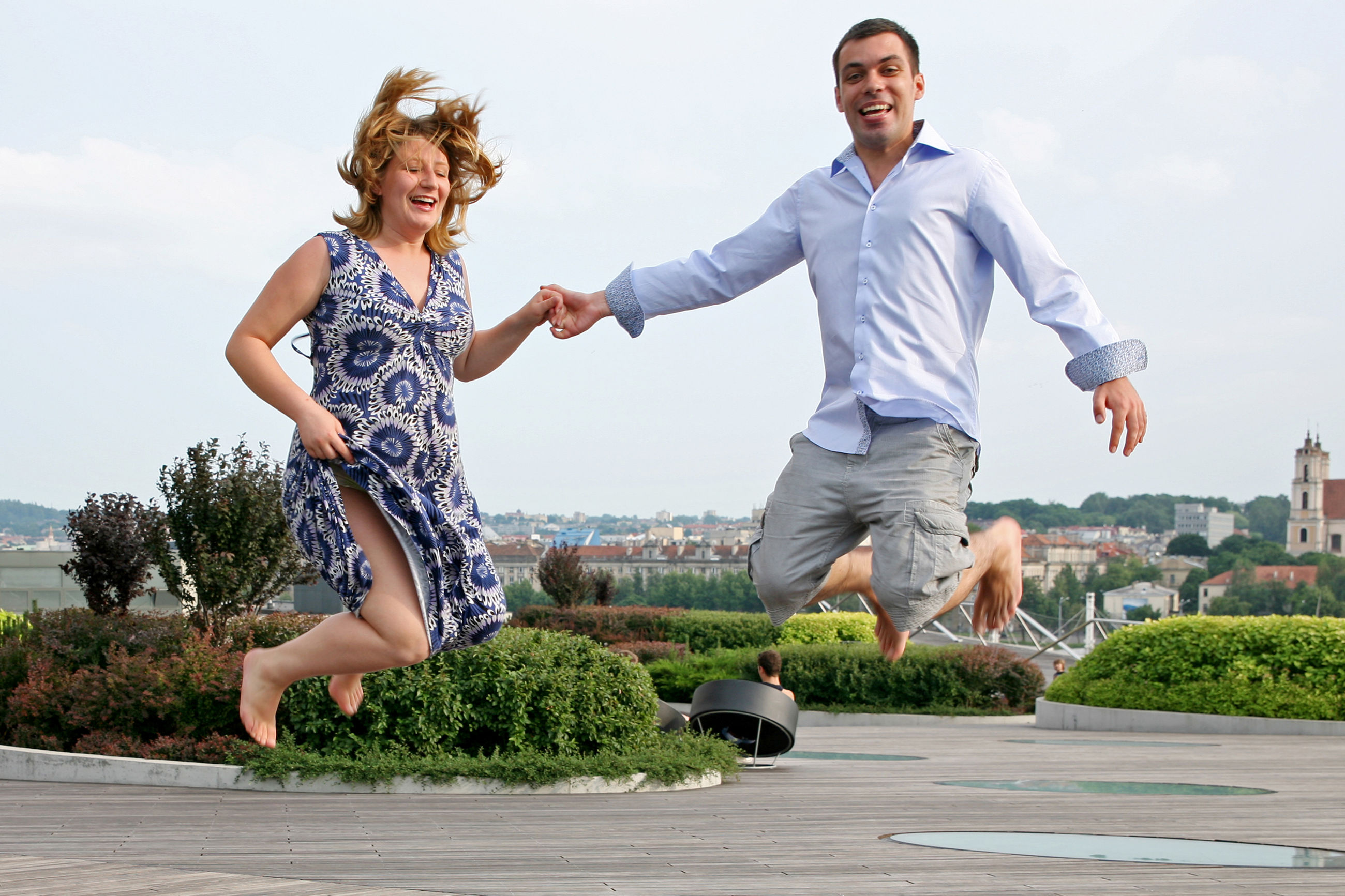 full length, leisure activity, casual clothing, real people, happiness, two people, smiling, fun, togetherness, lifestyles, jumping, mid-air, outdoors, day, young adult, mature men, young men, mature women, young women, enjoyment, architecture, playing, built structure, sky, bonding, childhood, tree, nature