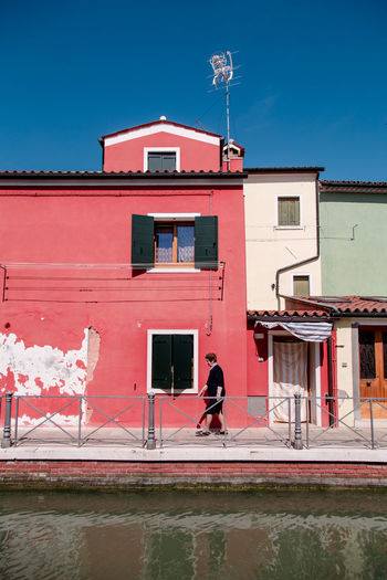 Burano Burano, Italy Burano, Venice Architecture Architecture_collection Architectural Detail Colours Lines Perspective Passing By Walking Portrait Of A Woman Red Window Sky Architecture Building Exterior Built Structure Residential Structure Residential District Street Scene Building Exterior