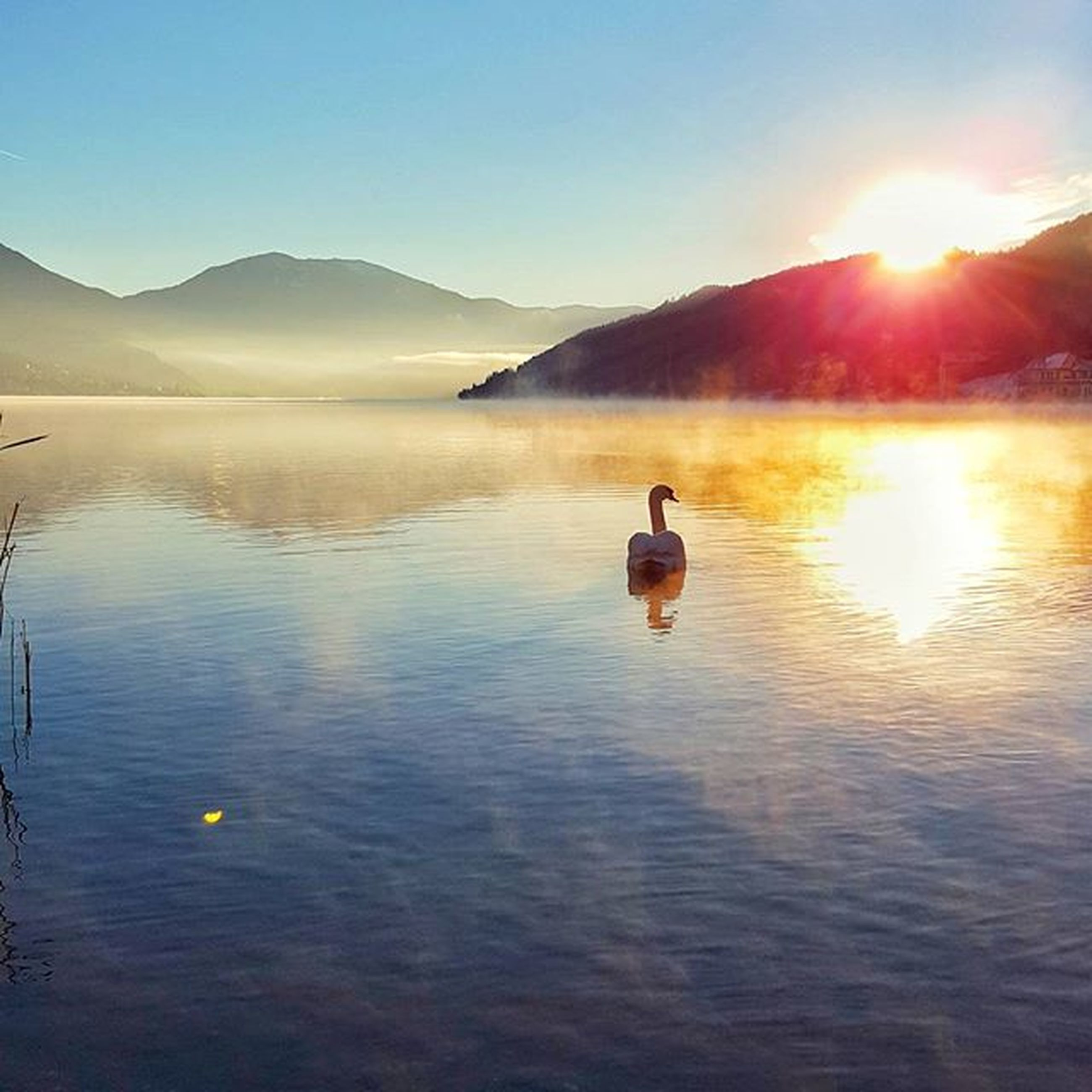water, mountain, sun, reflection, beauty in nature, lake, sunset, tranquility, scenics, tranquil scene, sunlight, waterfront, leisure activity, lifestyles, nature, mountain range, sky, clear sky