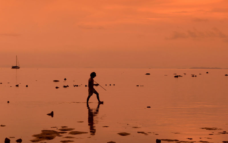 Full length of boy walking on beach during sunset