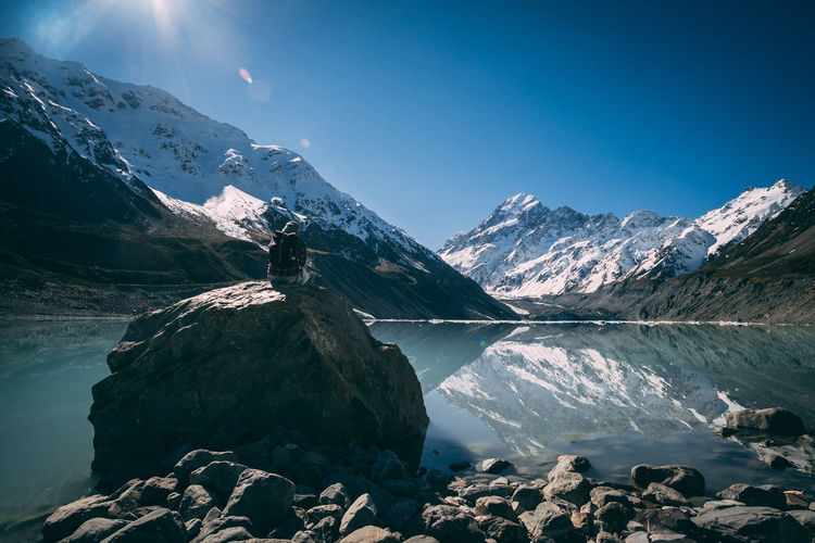 One man sitting on rock near the lake with snowcapped mountains reflection