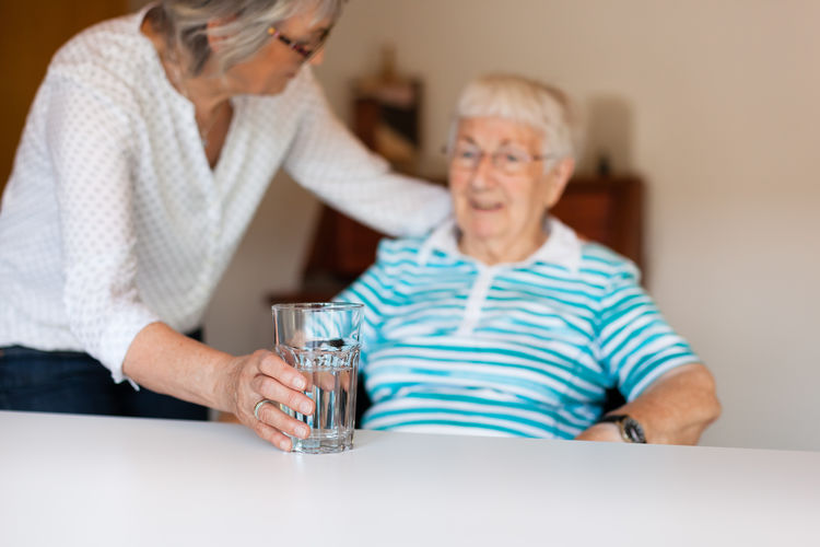 Senior Woman With Drinking Glass Looking At Sick Friend