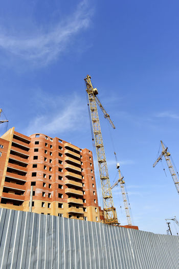 Low angle view of crane by buildings against blue sky