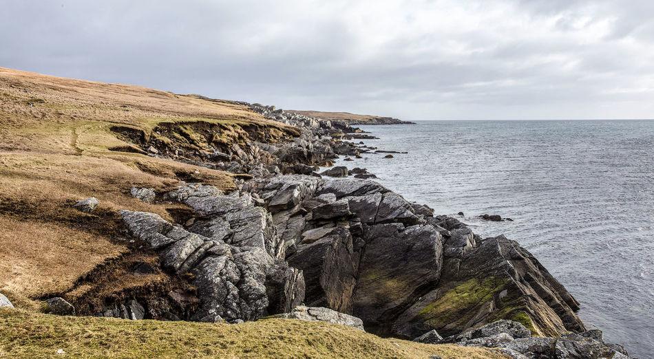 Photo taken in the UK, Scotland, Shetland, Yell Uk Scotland Shetland Sky Water Beauty In Nature Tranquility Sea North Sea Coatline Craggy Yell Horizon Over Water Cloud - Sky Horizon Rocky Coastline